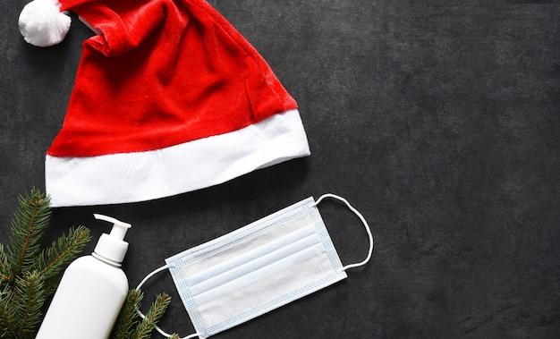 Bonnet De Noel, Masque Médical Et Antiseptique Sur Fond De Béton Noir. Photo Premium