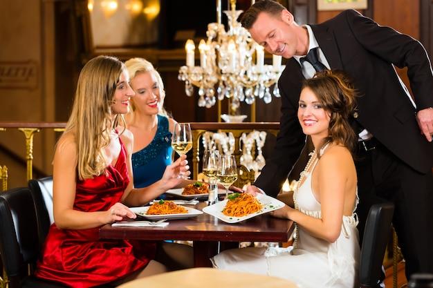 De bons amis pour déjeuner dans un bon restaurant, un serveur a servi le dîner Photo Premium