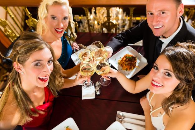 Bons amis pour le dîner ou le déjeuner dans un bon restaurant, cliquetis Photo Premium