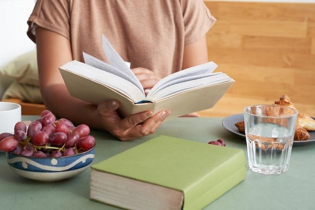 Bookworm prenant son petit déjeuner Photo gratuit