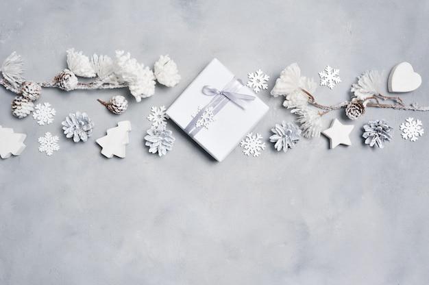 Border une carte de voeux de noël avec une boîte-cadeau de noël, des cônes, un cœur, des flocons de neige Photo Premium