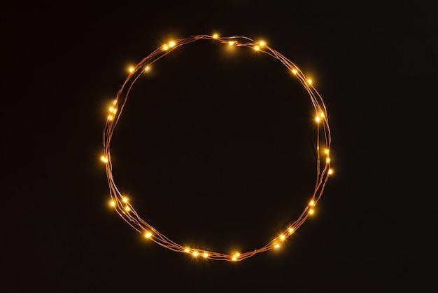 Bordure de guirlande de lumières de noël sur fond noir. Photo Premium