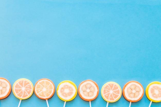 Bordure inférieure de sucettes de gelée sur fond bleu Photo gratuit