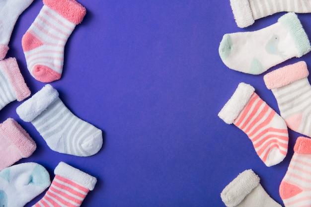 Bordure latérale faite avec différents types de chaussettes pour bébé sur fond bleu Photo gratuit
