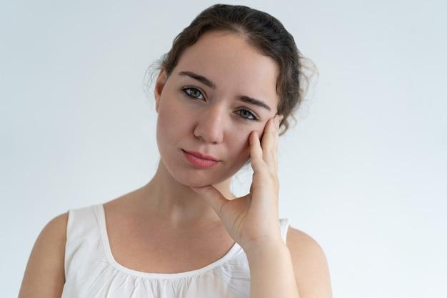 Bored belle femme touchant le visage Photo gratuit