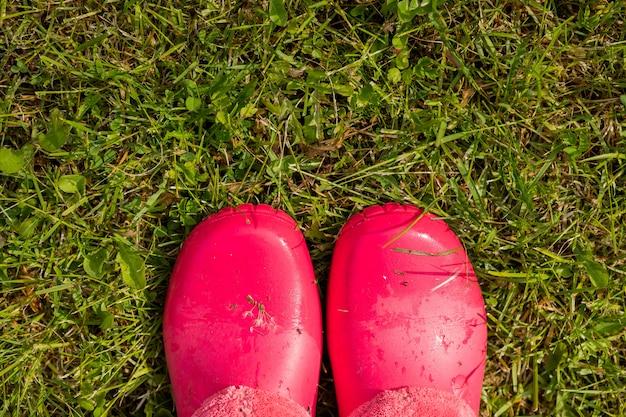 Bottes en caoutchouc debout dans le jardin après la pluie Photo Premium