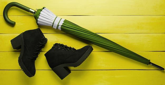 Bottes En Daim Noir, Parapluie Sur Fond De Bois Jaune. Vue De Dessus Photo Premium