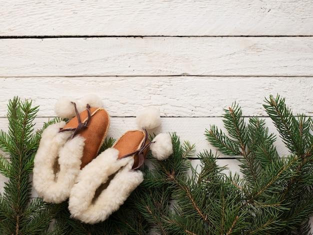 Bottes de noël bébé et arbre vert sur bois blanc, carte enfant hiver, fond Photo Premium