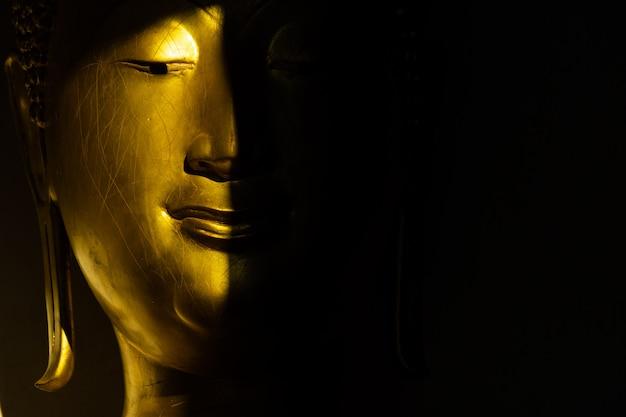 Bouche et visage, statue dorée de bouddha à la lumière et à l'ombre du soleil au temple wat pra sri mahathat Photo Premium