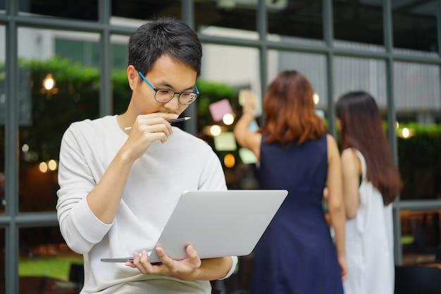 Bouchent Asiatique Concepteur Créatif Homme Pense Et Travaille Au Bureau Avec L'équipe Photo Premium