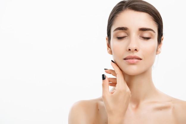Bouchent belle jeune femme touchant sa peau sur fond blanc. Photo Premium