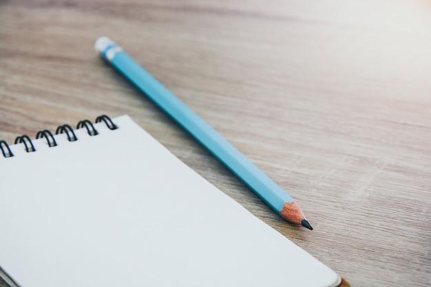 Bouchent cahier ouvert vide et crayon de couleur bleue sur fond de table en bois Photo Premium