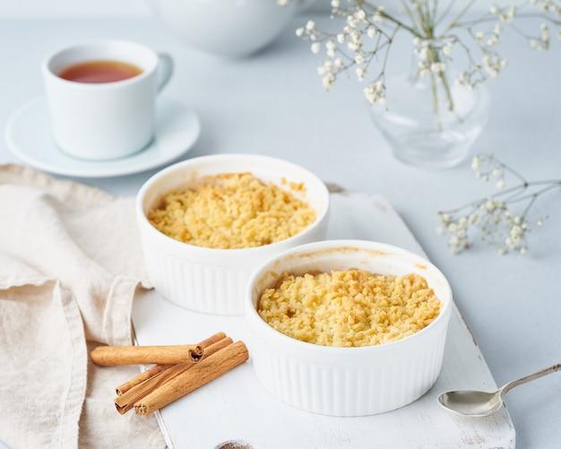 Bouchent crumble aux pommes avec streusel. vue de côté. petit déjeuner le matin sur une table gris clair. Photo Premium
