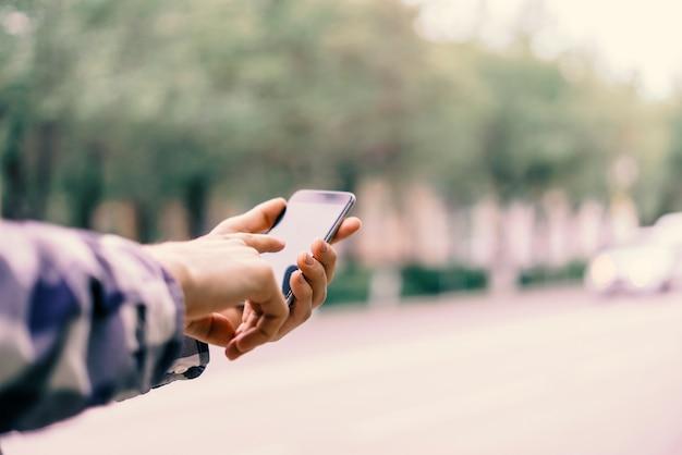 Bouchent Les Doigts De La Main Touchant Le Smartphone Dans La Ville Photo Premium