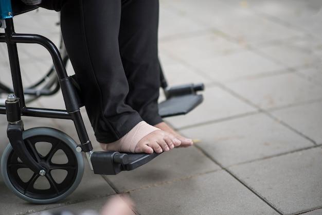 Bouchent les douleurs des pieds âgés assis sur un fauteuil roulant Photo gratuit