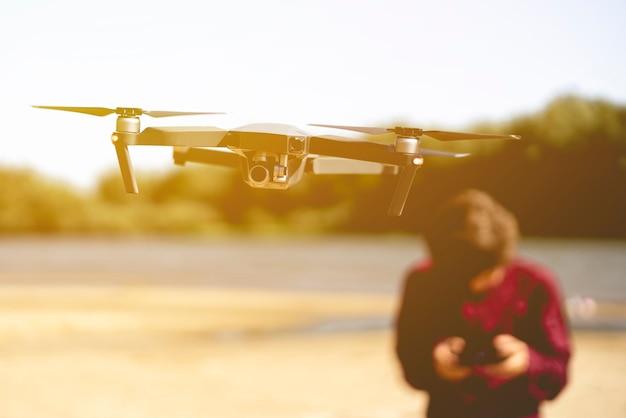 Bouchent drone volant dans les airs avec homme avec contrôleur sur le fond. Photo Premium