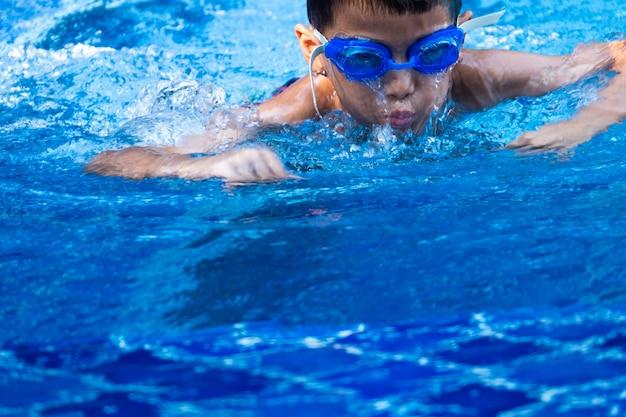 Bouchent le garçon asiatique ware un bleu lunettes plongeant et nageant dans la piscine et l'eau bleue rafraîchissante. Photo Premium