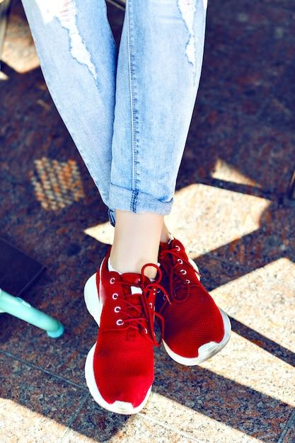 Bouchent L'image De Mode Des Pieds De La Femme, Portant Des Jeans Vintage Et Des Baskets Rouges élégantes, Des Couleurs Vives. Photo gratuit