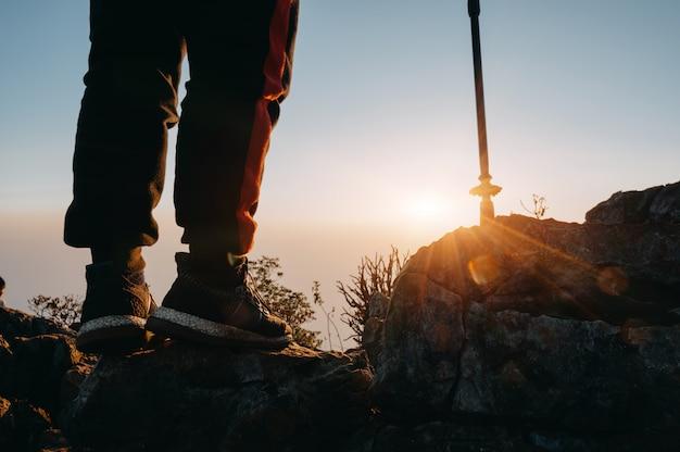 Bouchent les jambes de l'homme de la randonnée se tenir sur la montagne avec la lumière du soleil. Photo Premium