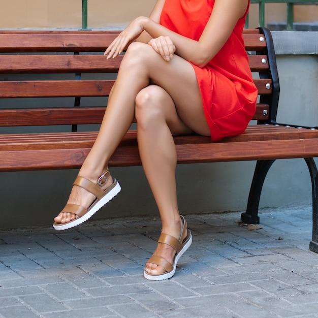 Bouchent Les Jambes Nues D'une Femme Musclée En Robe Rouge Courte Assis Sur Un Banc En Bois Photo Premium