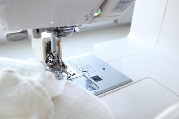 Bouchent la machine à coudre avec du textile blanc au lieu de travail. coudre le processus. - concept de couture, d'artisanat, de couture et de couture. Photo Premium