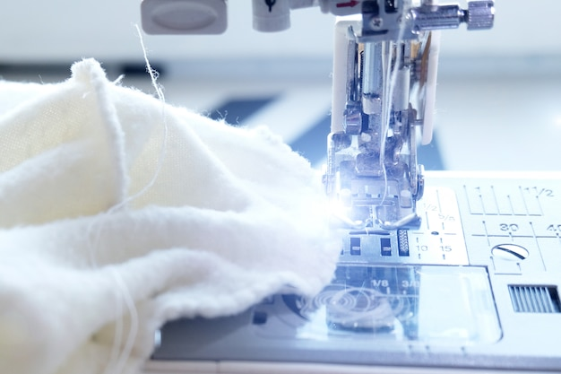Bouchent La Machine à Coudre Avec Du Textile Blanc Sur Le Lieu De Travail Photo Premium