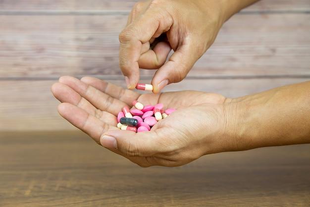 Bouchent La Main Choisissez Une Capsule De Médicament. Photo Premium