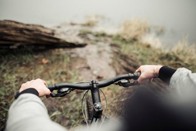 Bouchent les mains du cycliste sur un guidon de vélo de montagne Photo gratuit