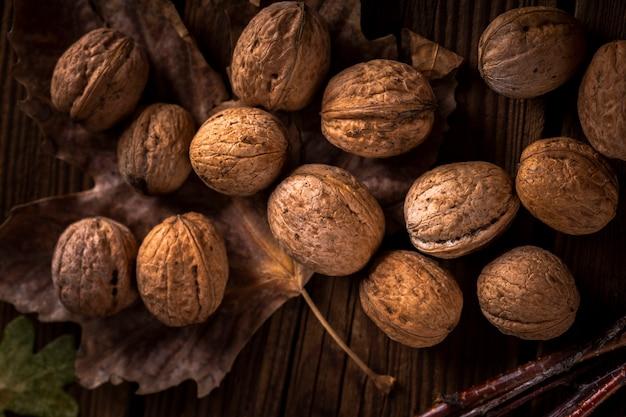 Bouchent les noix sur une table en bois avec des feuilles Photo gratuit