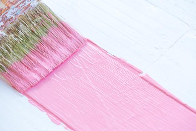 Bouchent le pinceau peinture couleur rose sur une table en bois blanche. Photo Premium