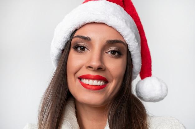 Bouchent Portrait Belle Femme Caucasienne En Bonnet Rouge Sur Mur Blanc. Concept De Noël Nouvel An. Dents De Femme Mignonne Souriant Des émotions Positives Avec Copie Gratuite Photo Premium