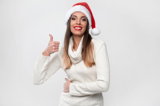Bouchent Portrait Belle Femme Caucasienne En Bonnet Rouge Sur Mur Blanc. Concept De Noël Nouvel An. Dents De Femme Mignonne Souriant émotions Positives Montrant Les Pouces Vers Le Haut Photo Premium