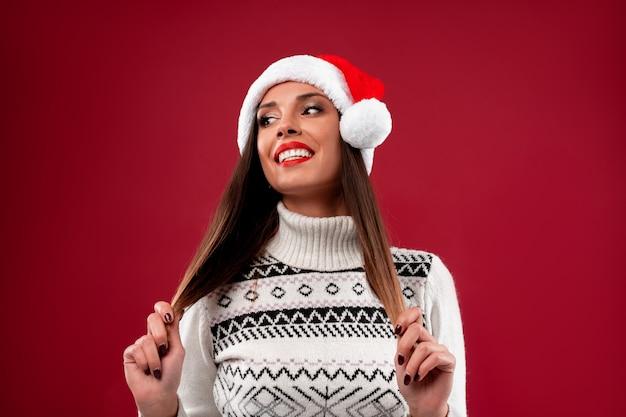 Bouchent Portrait Belle Femme Caucasienne En Bonnet Rouge Sur Mur Rouge. Concept De Noël Nouvel An. Dents De Femme Mignonne Souriant Des émotions Positives Touche Les Cheveux Avec Un Espace De Copie Gratuit Photo Premium