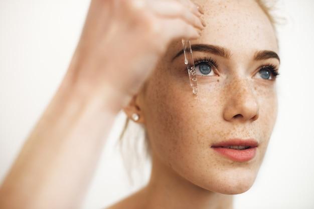 Bouchent Le Portrait D'une Charmante Femme Aux Cheveux Rouges Avec Des Taches De Rousseur Appliquant Le Sérum Hyaluronique Sur Son Visage Isolé Sur Blanc. Photo Premium