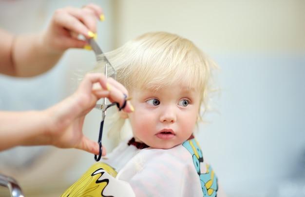 Bouchent le portrait d'un enfant en bas âge faisant sa première coupe de cheveux Photo Premium
