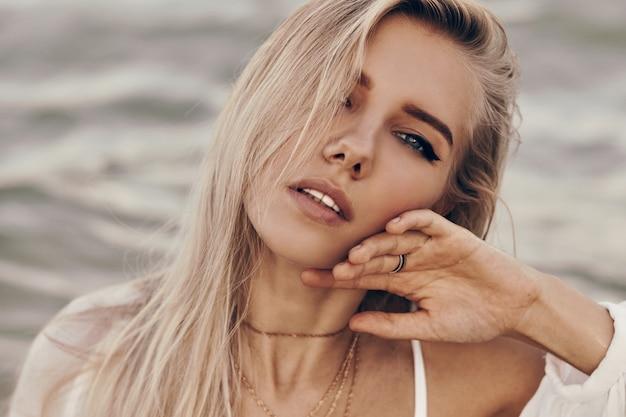 Bouchent Le Portrait D'une Femme Blonde Magnifique Avec Une Peau Parfaite Et Des Yeux Bleus Posant Sur La Plage Photo gratuit