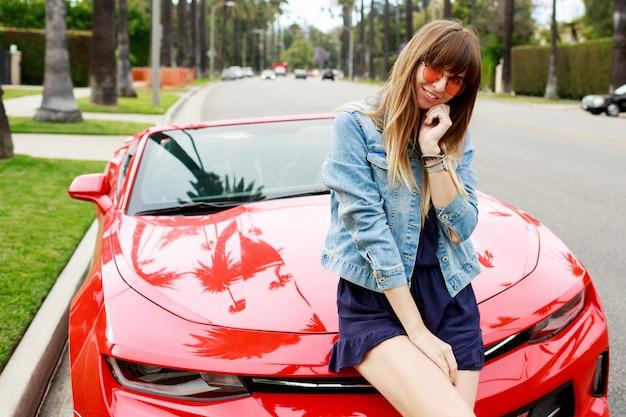 Bouchent Le Portrait D'une Femme Brune Surprise Assise Sur Le Capot D'une Incroyable Voiture De Sport Décapotable Rouge En Californie. Photo gratuit