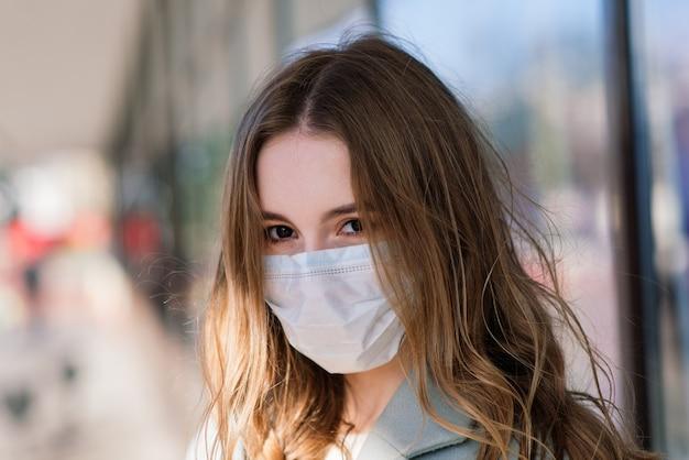Bouchent Le Portrait D'une Femme Portant Un Masque Médical Et Debout Dans La Rue Contre D'un Café Photo Premium