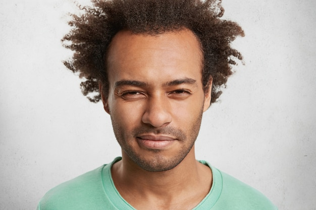 Bouchent Le Portrait D'un Homme Suspect à La Peau Sombre Porte Un Pull Vert, A Une Expression Sérieuse Photo gratuit