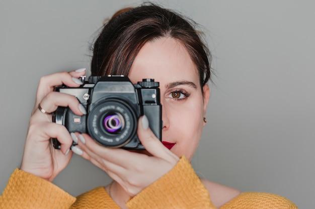 Bouchent Le Portrait D'une Jeune Femme Tenant Un Appareil Photo. Concept De Photographie Photo Premium