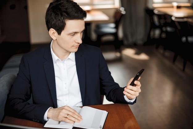 Bouchent Le Portrait D'un Jeune Homme D'affaires Caucasien En Regardant Son Smartphone Assis à Un Bureau Avec Une Main Sur Un Ordinateur Portable. Photo Premium