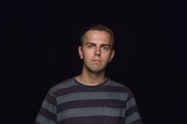 Bouchent Le Portrait De Jeune Homme Isolé Sur Mur Noir Photo gratuit