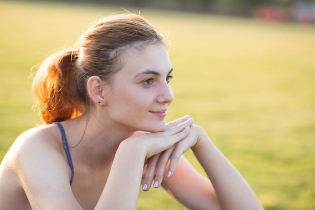 Bouchent Le Portrait De Joyeuse Jeune Fille Souriante Avec Des Taches De Rousseur Sur Son Visage à L'extérieur En Journée D'été Ensoleillée. Expressions Et émotions Humaines. Photo Premium