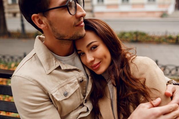 Bouchent Le Portrait Romantique Du Jeune Beau Couple Amoureux étreignant Sur Un Banc En Automne Parc. Porter Un élégant Manteau Beige. Photo gratuit