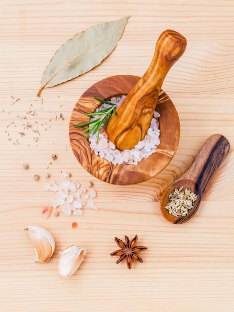 Bouchent sel rose de l'himalaya dans un mortier en bois et des herbes sur fond de bois. Photo Premium