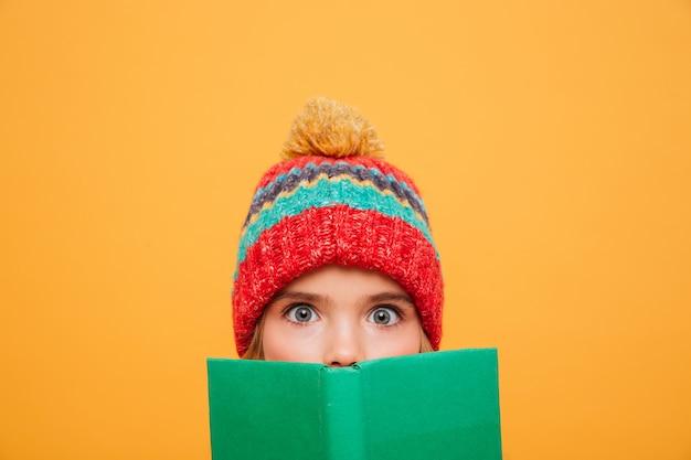 Bouchent Surpris Jeune Fille En Pull Et Chapeau Se Cachant Derrière Le Livre Et Regardant La Caméra Sur Orange Photo gratuit