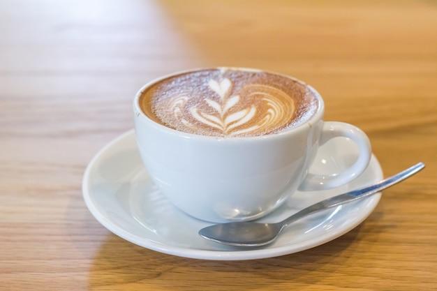 Bouchent la tasse de café blanc et café latte placé sur des planchers Photo Premium