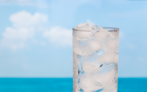 Bouchent le verre de rafraîchissement de boire de l'eau avec de la glace sur le ciel de la mer de l'été Photo Premium