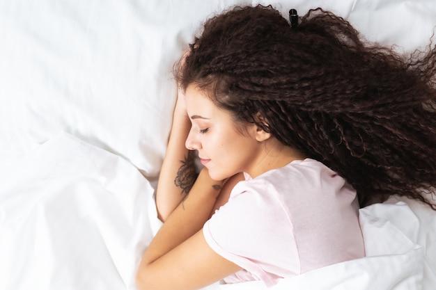 Bouchent La Vue De Dessus De La Belle Femme De Cheveux Afro Dormant à Des Draps Blancs Comme Neige Allongé Sur Un Grand Lit. Copyspace. Photo Premium