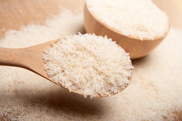 Bouchent la vue du riz dans une cuillère en bois et un bol sur le concept de fond, biologique et sain en bois. Photo Premium